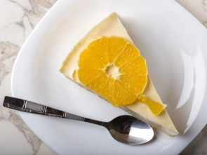 One slice of homemade orange cake on plate with teaspoon