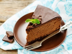 chocolate cheesecake with chocolate glaze on dark wood background. tinting. selective focus